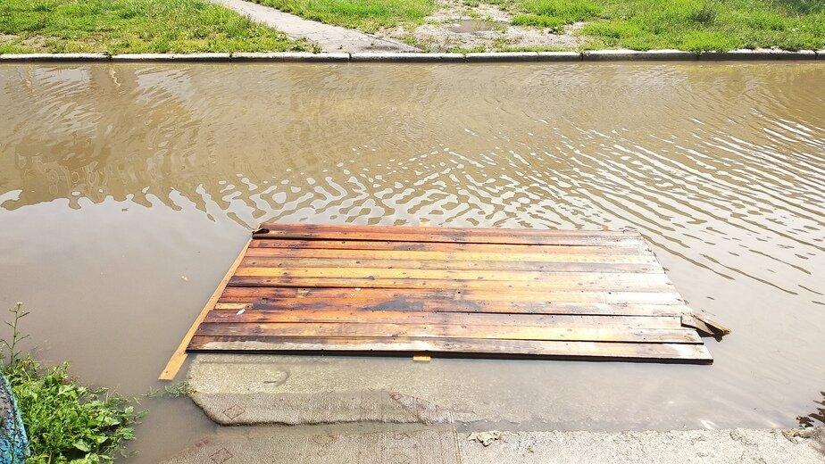 В Балтийске жители затопленного из-за дождя двора соорудили деревянные переправы - Новости Калининграда   Фото: Татьяна Ступак