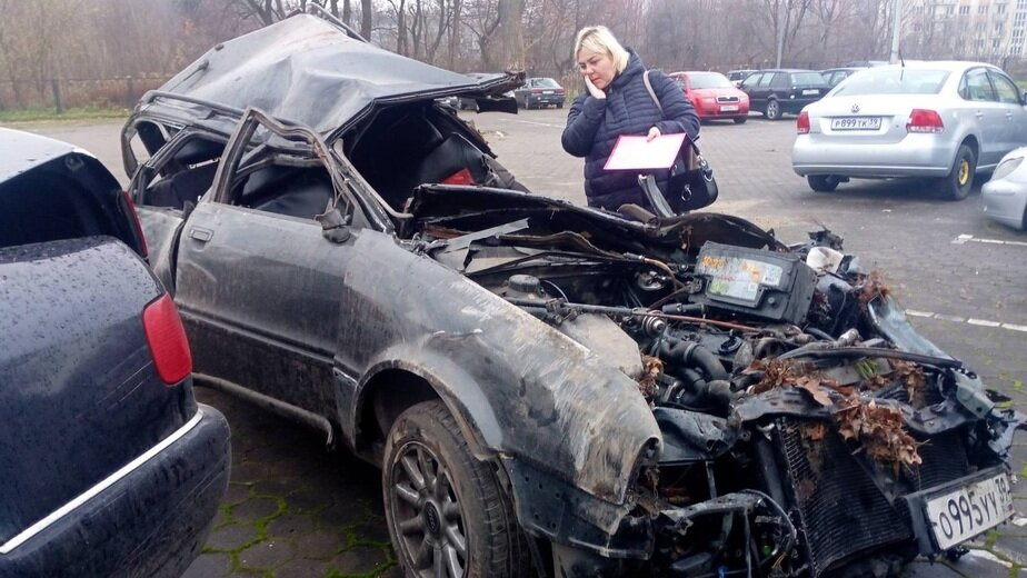 На фото: Юлия около остатков машины, в которой погибли Павел Коваленко и Андрей Галушка | Фото: Юлия Коваленко